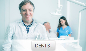 Middle-aged Smiling Dentist with Dental Assistant and Patient in Background